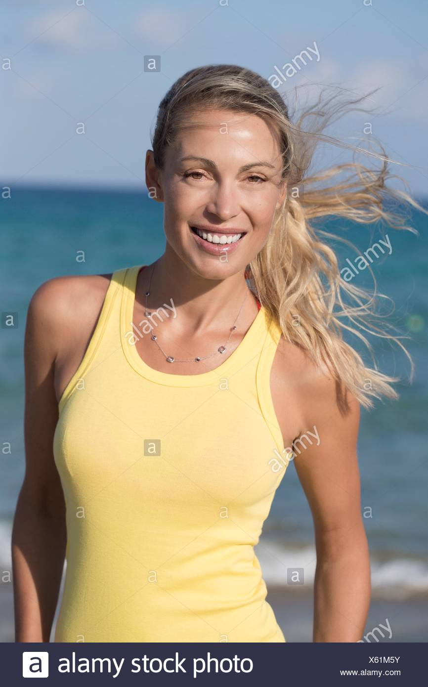 c3ac8adfa4b53 Portrait of smiling blond woman with yellow tank top Stock Photo ...