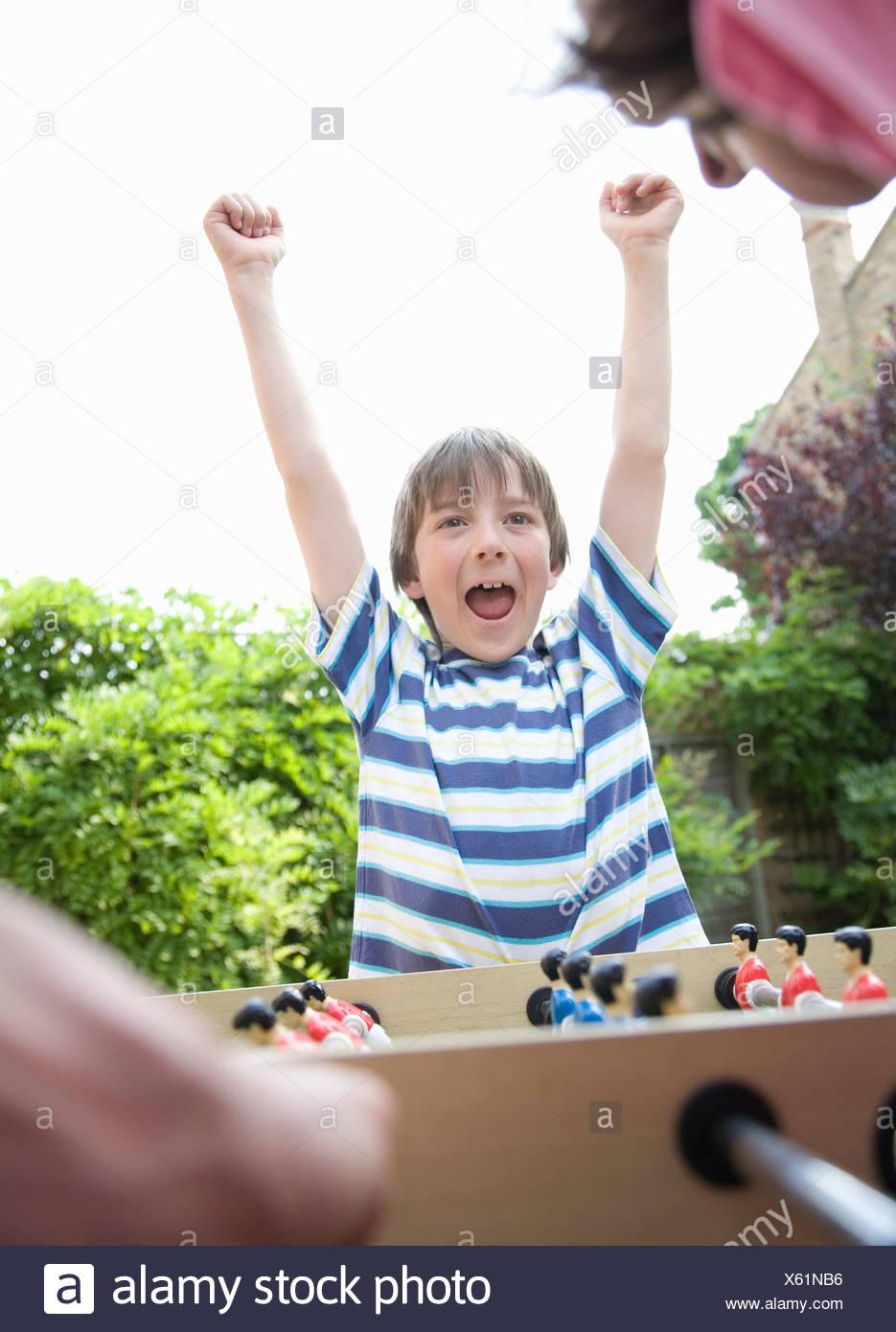 Boy celebrating, playing table football - Stock Image