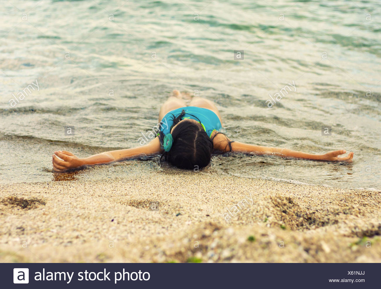 Little girl (6-7) lying on beach in waves - Stock Image
