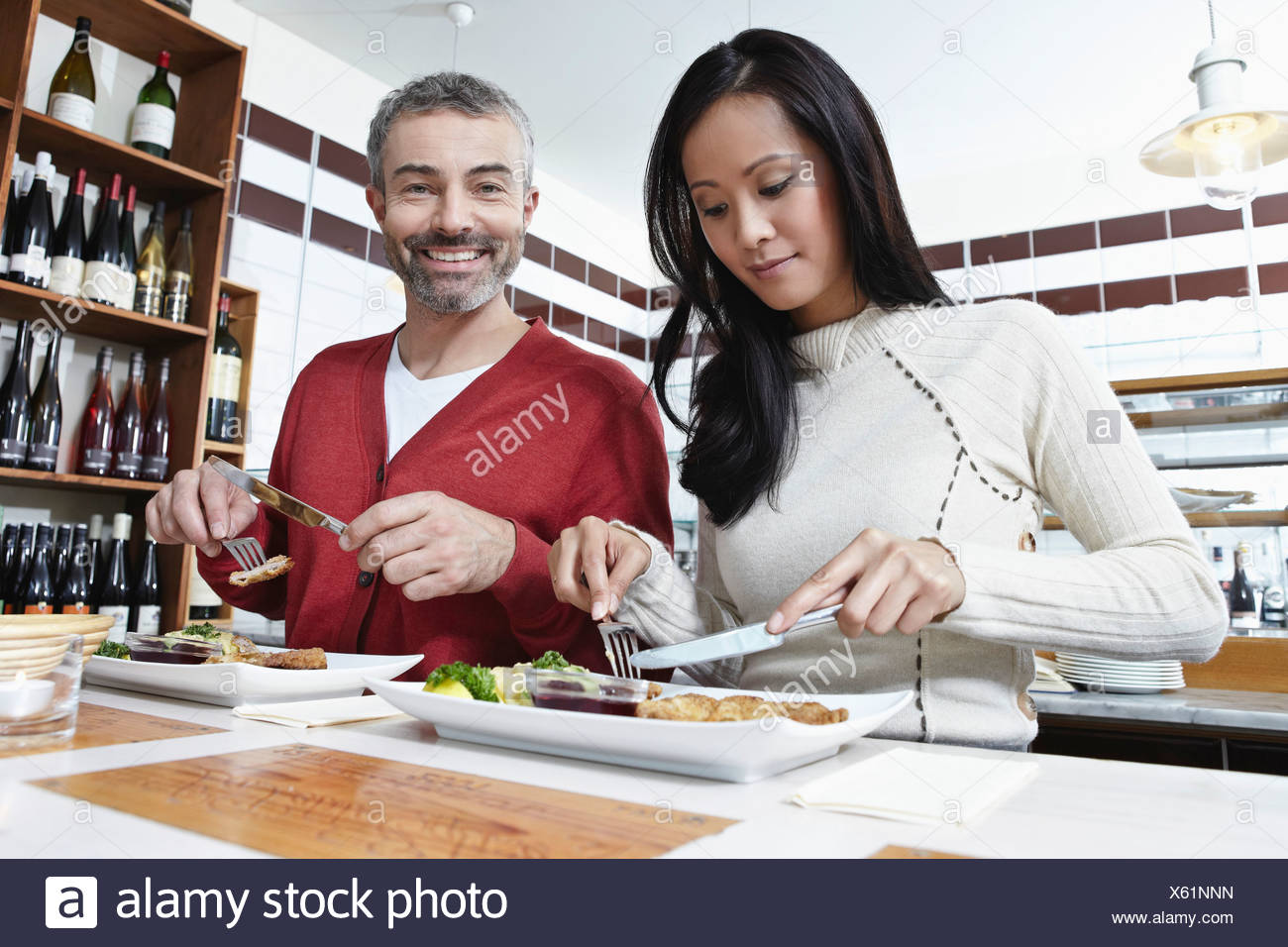 Germany, Cologne, Couple eating food in kitchen, smiling Stock Photo
