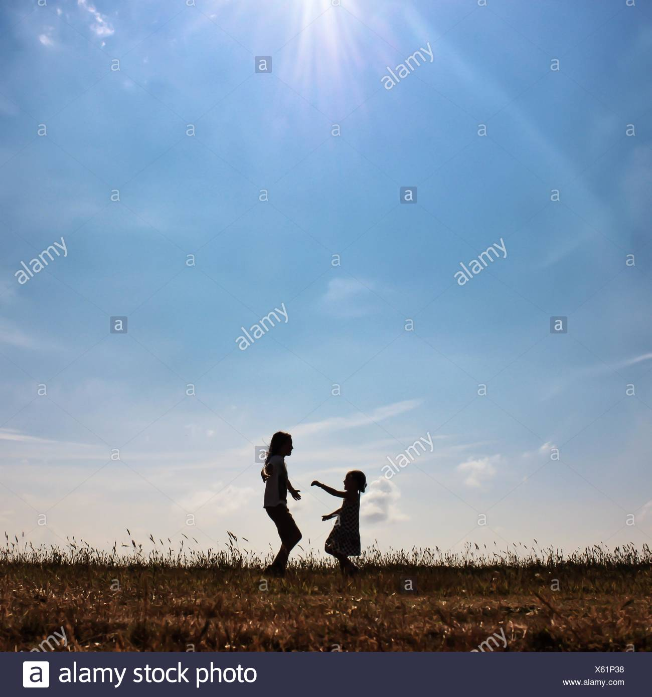 Silhouette of two girls playing in  a meadow - Stock Image