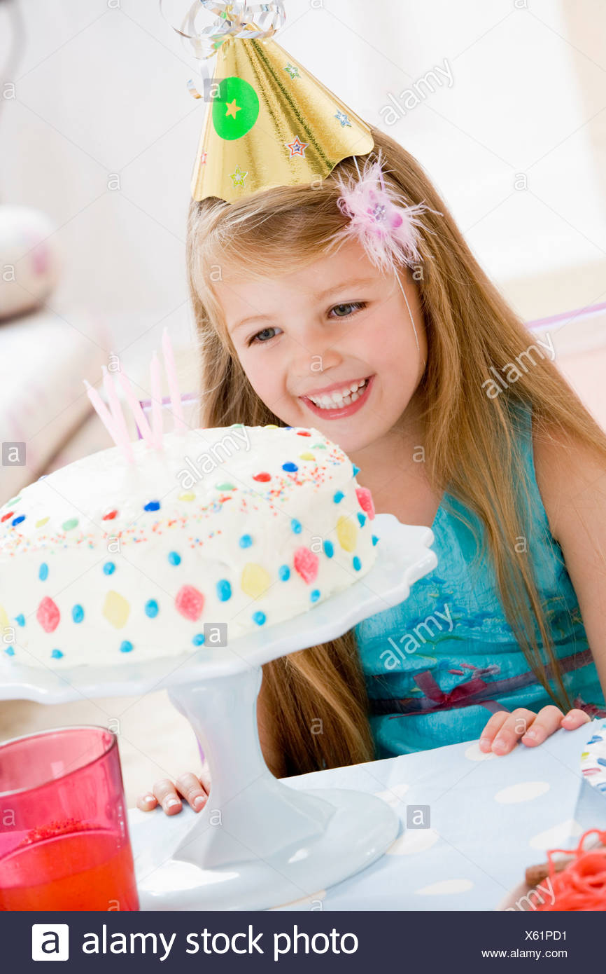 Young girl wearing party hat looking at birthday cake smiling - Stock Image