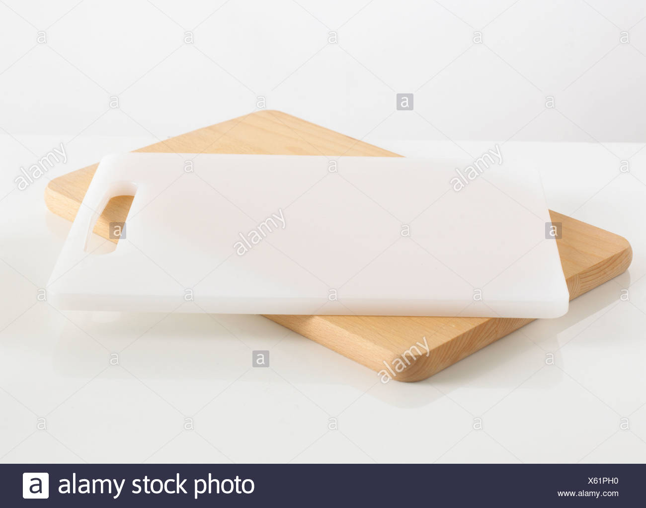 Wooden and white chopping board against white background - Stock Image