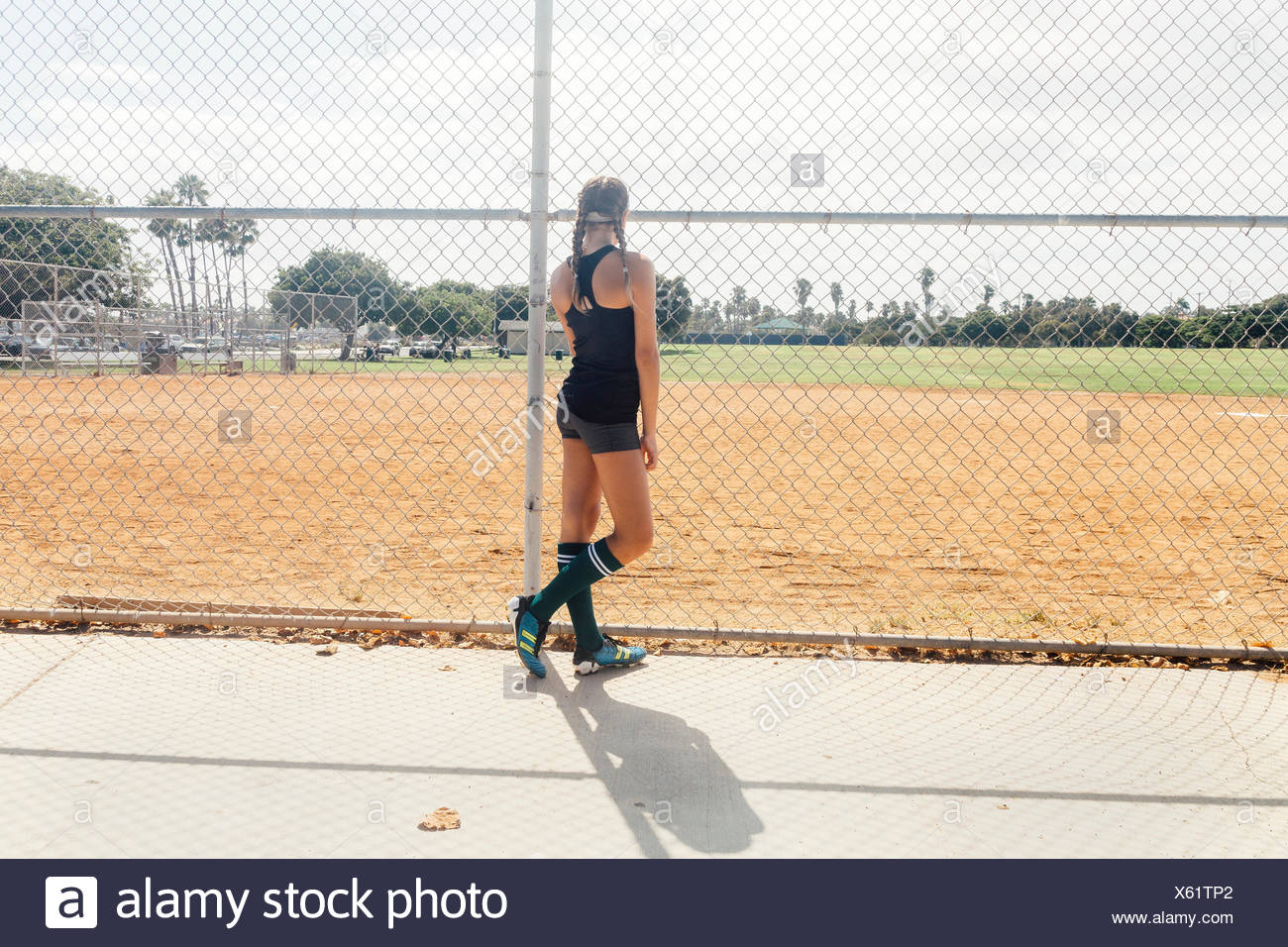 Schoolgirl soccer player at wire fence on school sports field - Stock Image