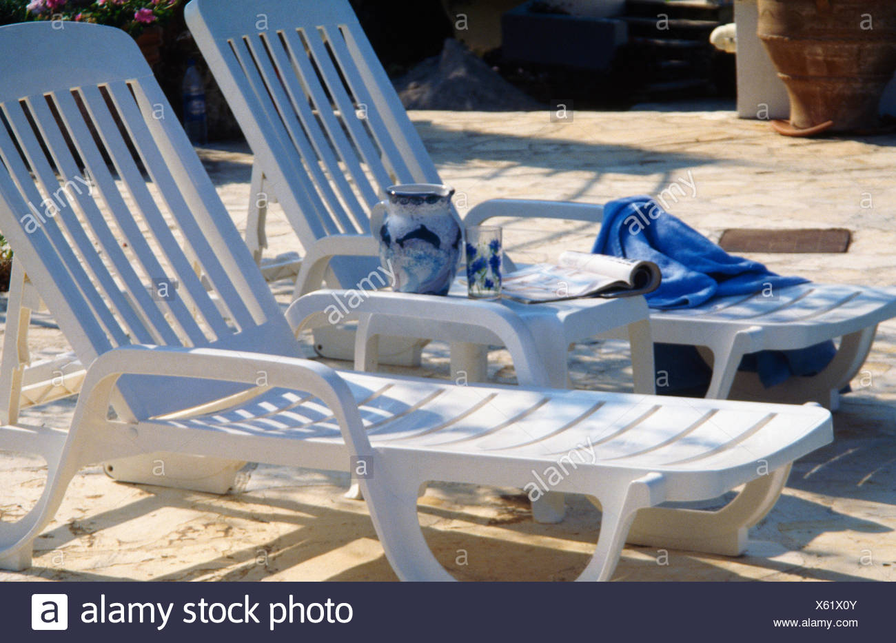White plastic loungers on paved patio - Stock Image