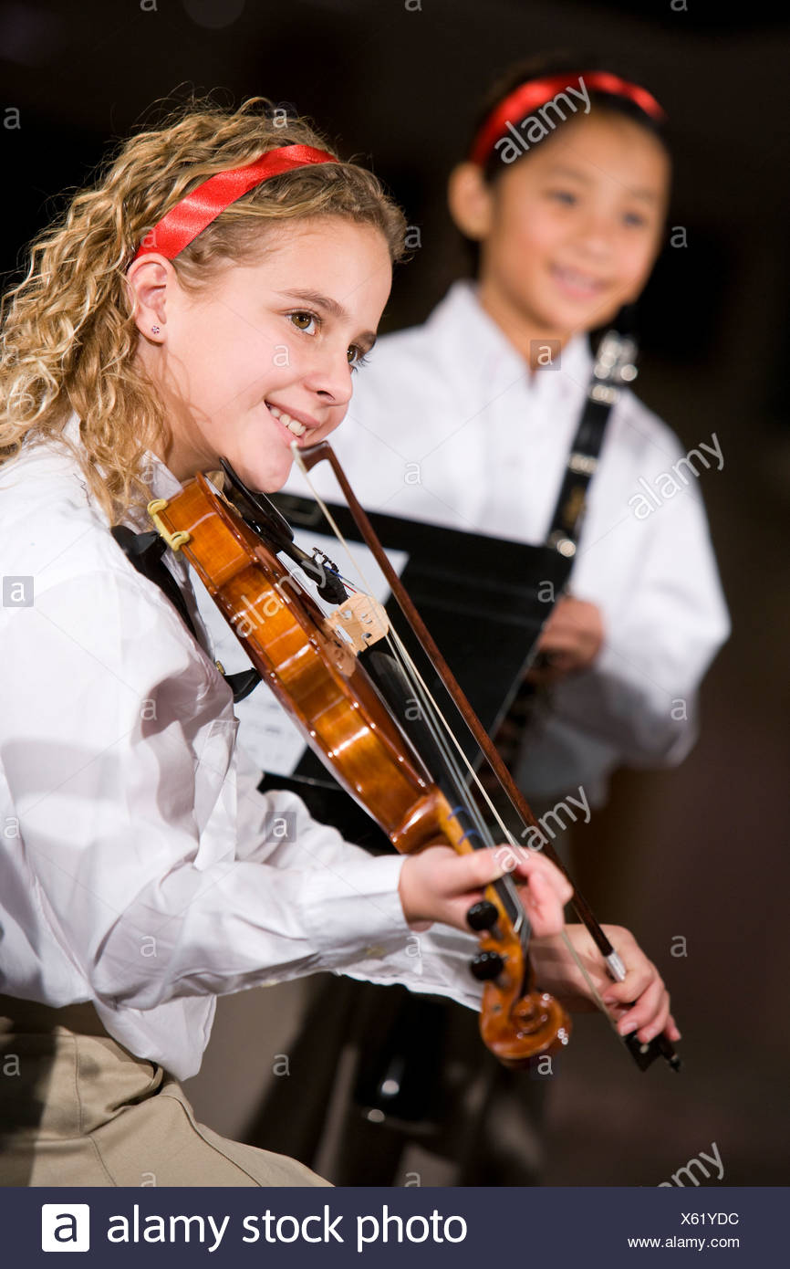 School children playing musical instruments, focus on girl with violin - Stock Image