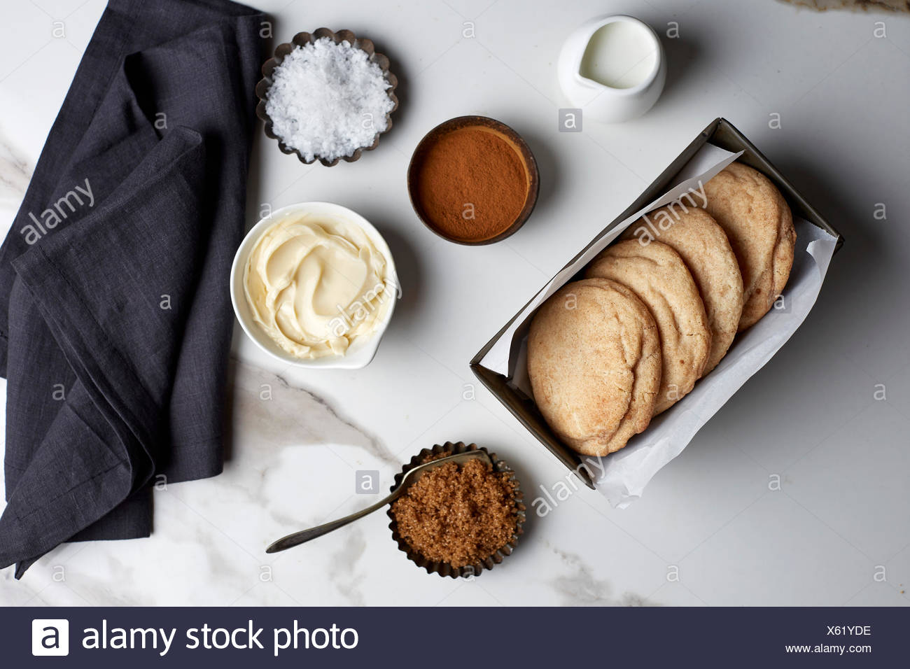Snickerdoodle cookies with ingredients in vintage tins on a white marble table and black linen - Stock Image