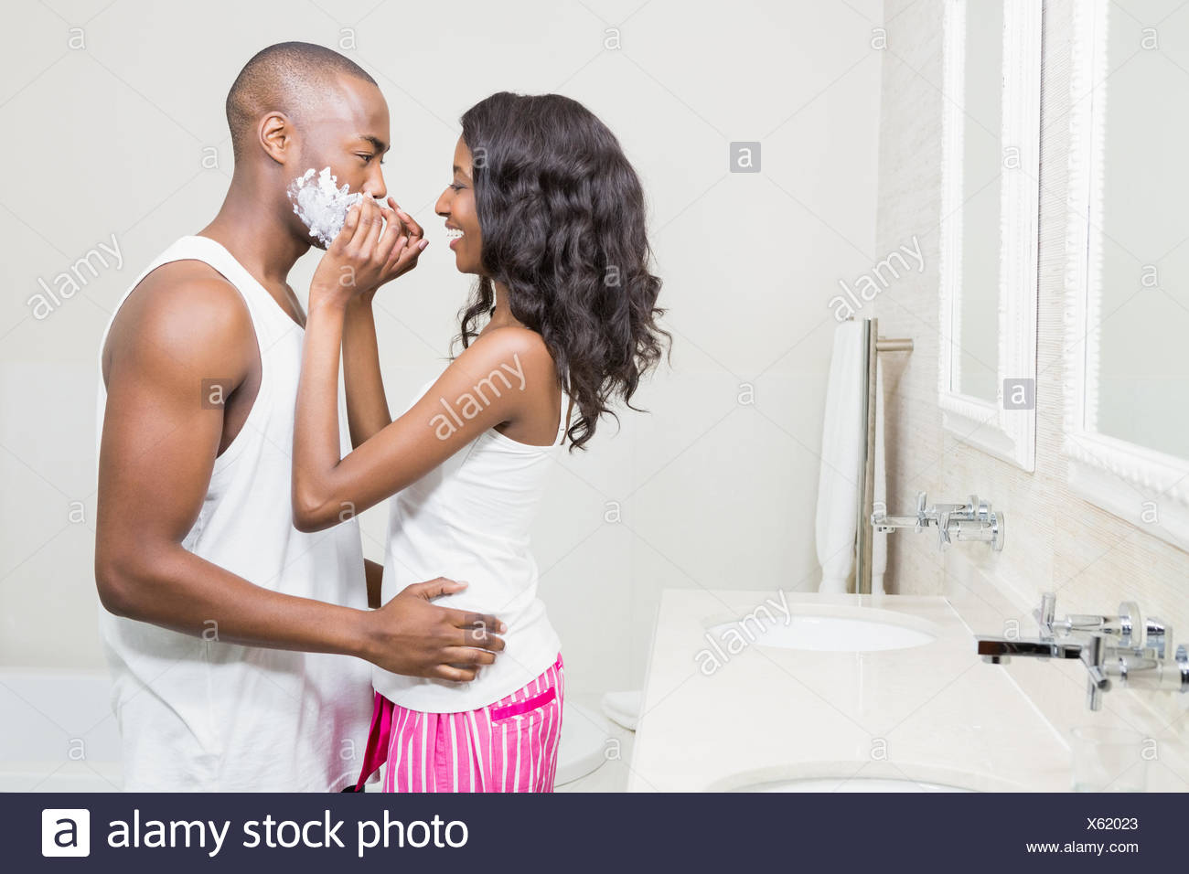 Young woman applying shaving cream on young mans face - Stock Image