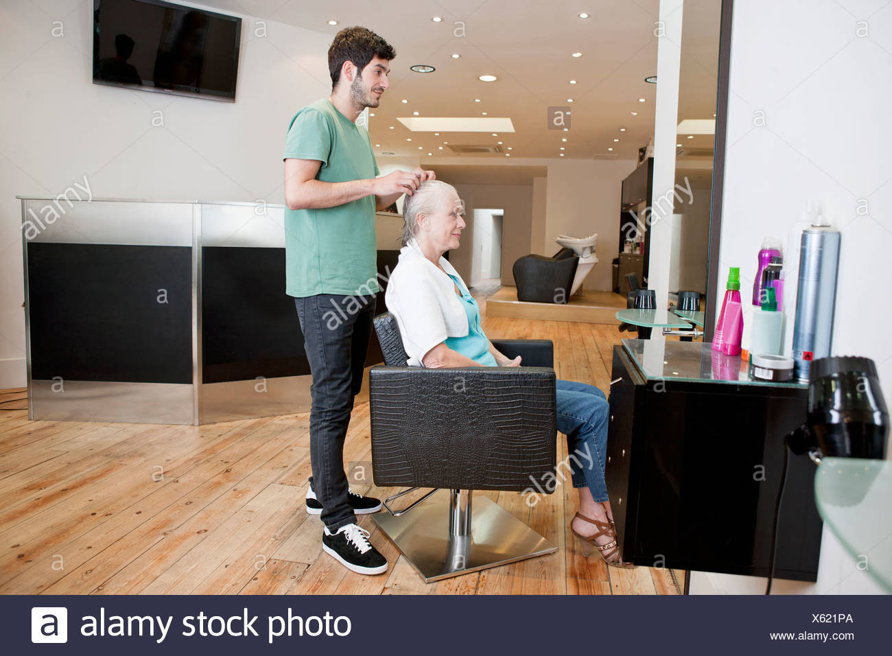 A male hairdresser applying product to his female clients hair - Stock Image