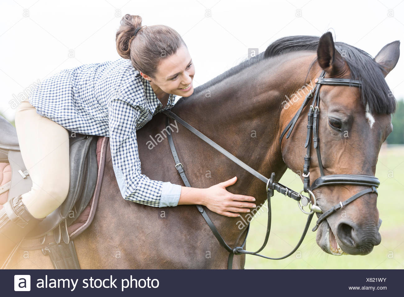 Smiling woman horseback riding leaning and petting horse - Stock Image
