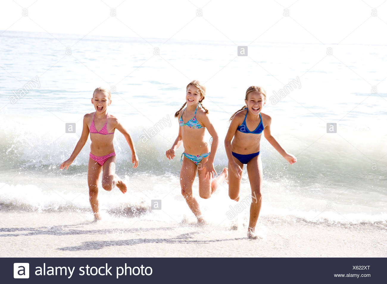 Three young girls running out of the sea Stock Photo
