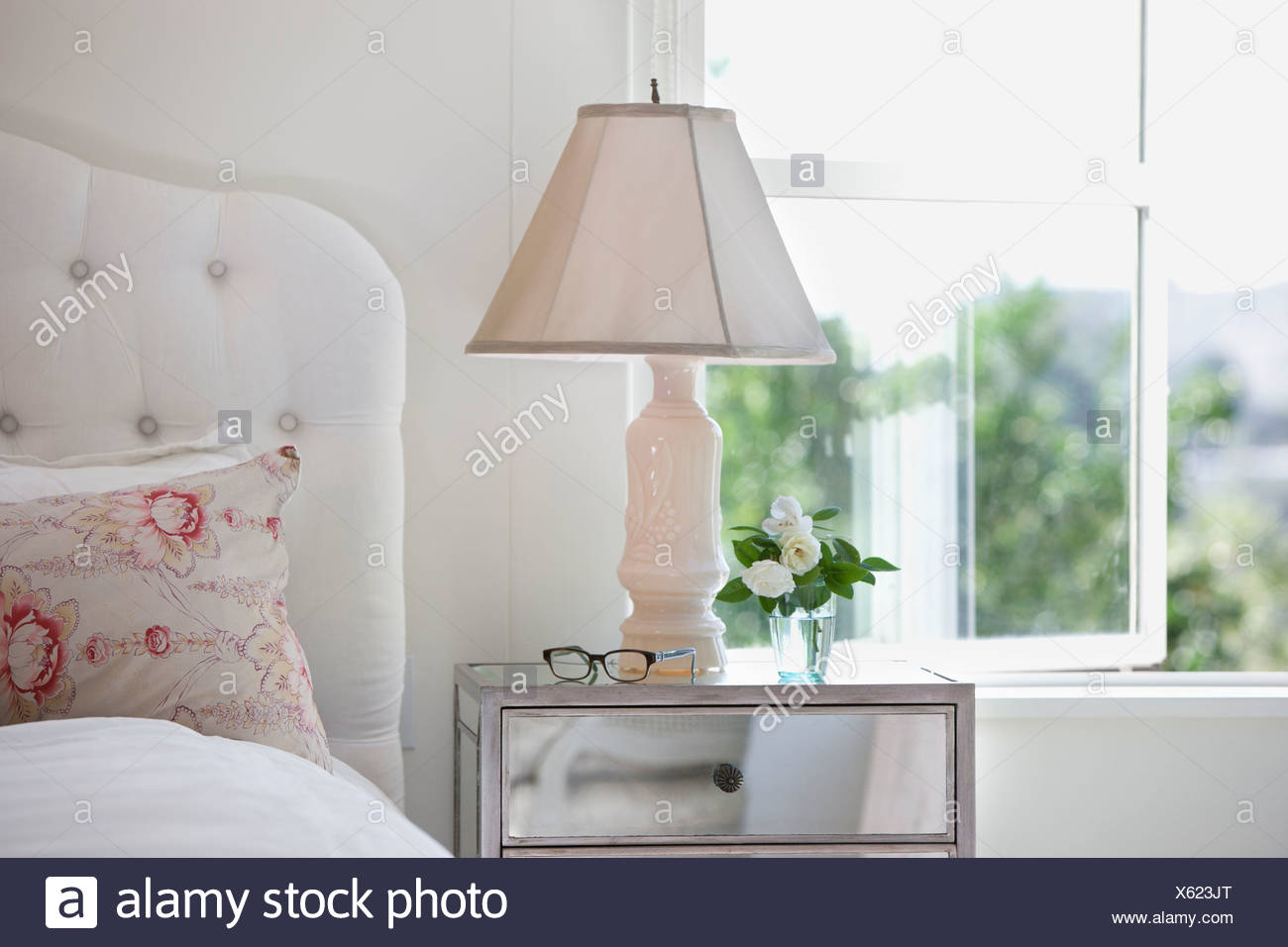 Bedside table and lamp in bedroom - Stock Image