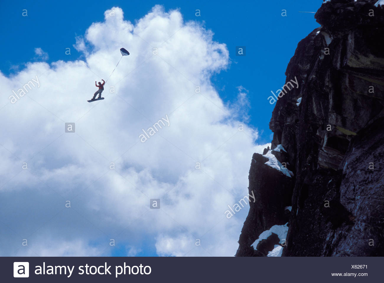 Snowboard-BASE jumper doing a backflip off a cliff near Lake Tahoe. - Stock Image