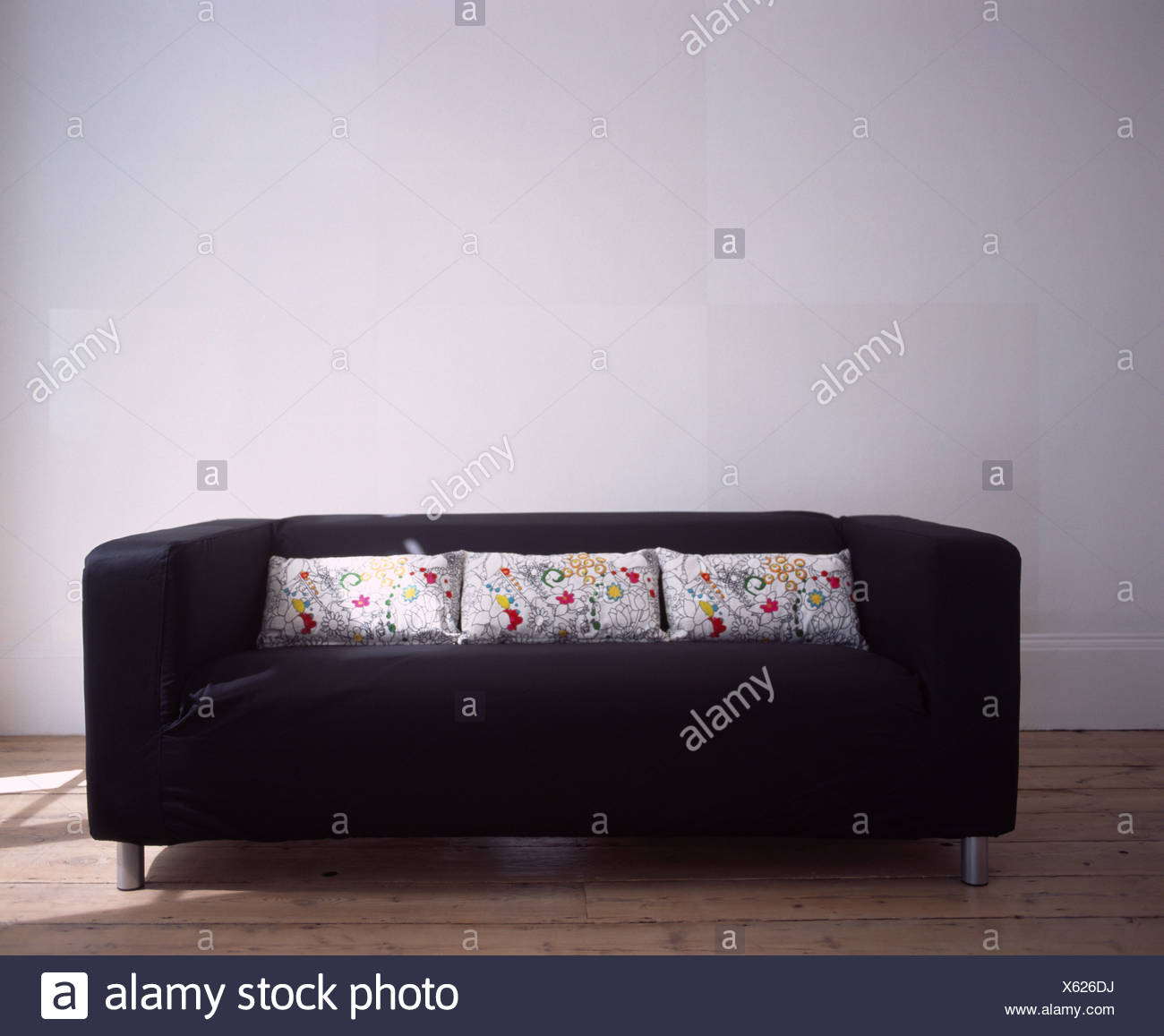 Modern black sofa with floral patterned cushions - Stock Image