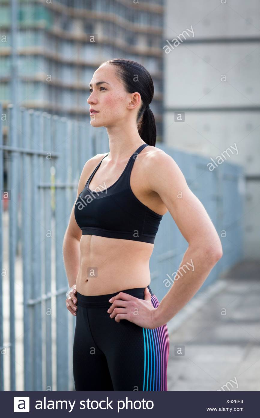 MODEL RELEASED. Young woman in crop top with hands on hips. - Stock Image
