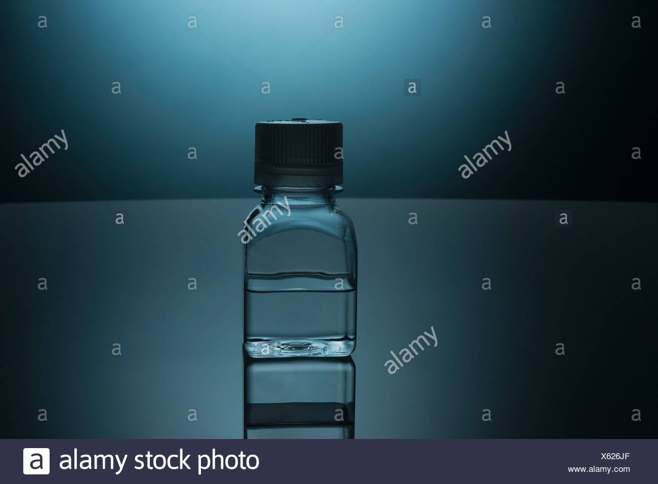 Glass bottle of clear liquid - Stock Image