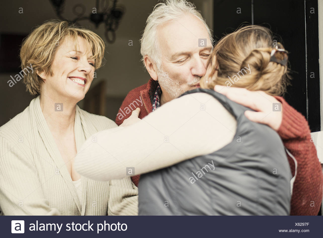 Father kissing adult daughter, mother smiling - Stock Image