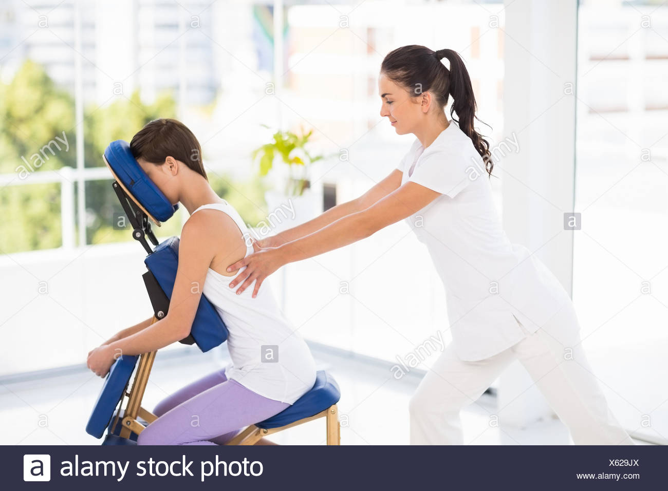 Woman being massaged on chair by masseuse Stock Photo