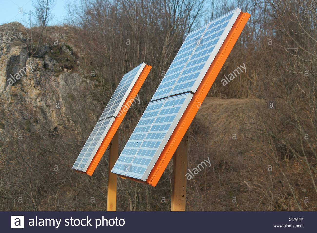 Solar Panels On Field Against Mountain - Stock Image