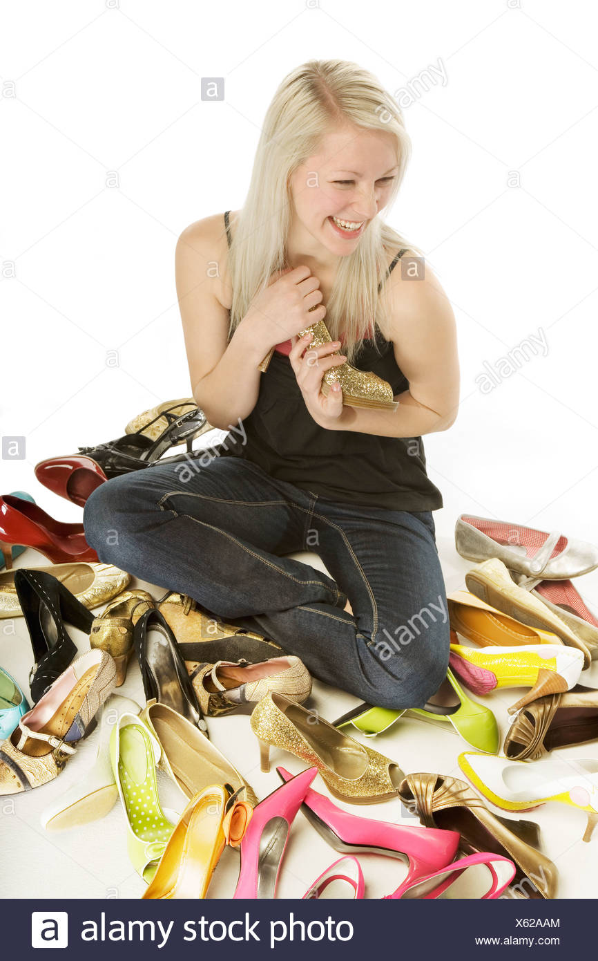 Woman holding high heel shoe while sitting in midst of many pairs - Stock Image