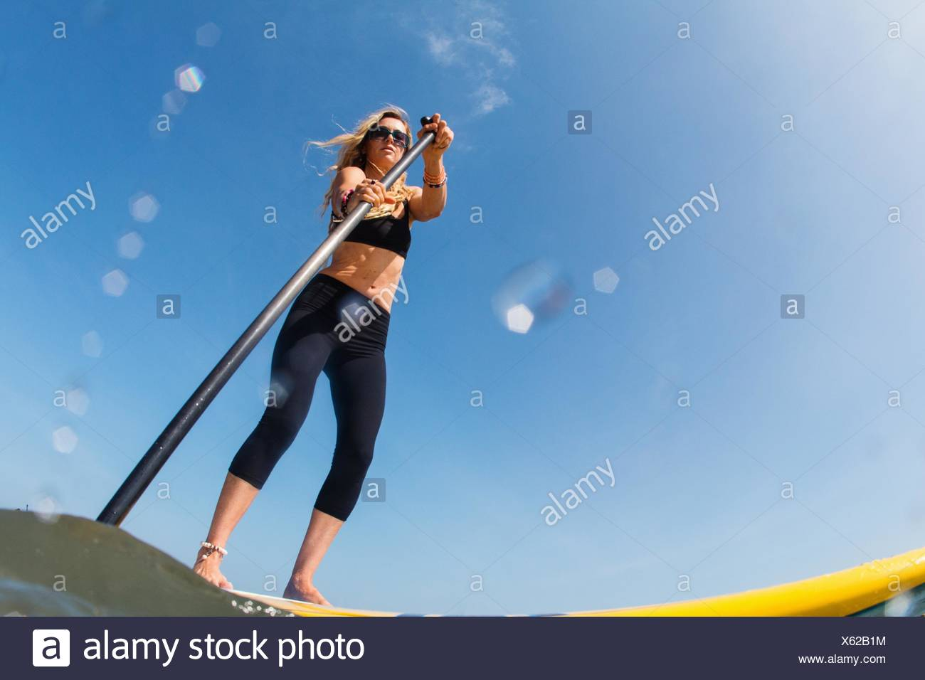 Low angle view of mid adult woman standup paddleboarding - Stock Image