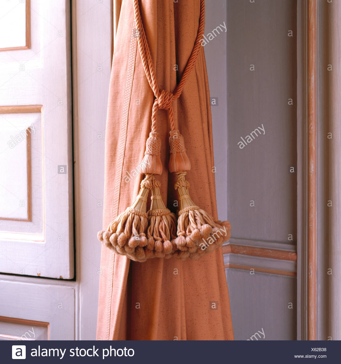 Close-up of peach curtain with toning silk tasseled tie back - Stock Image