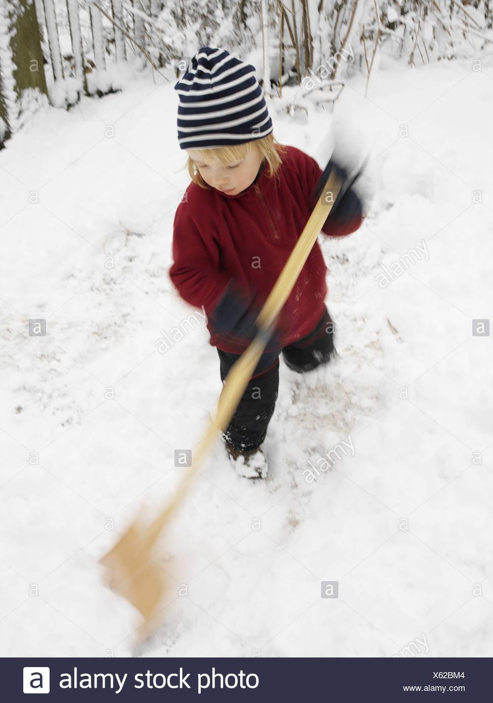 Give birth winter-clothing snow-shovels 4 years child blond ski-pants sweaters cap snow-shovel shovel shovels snow-evacuates - Stock Image