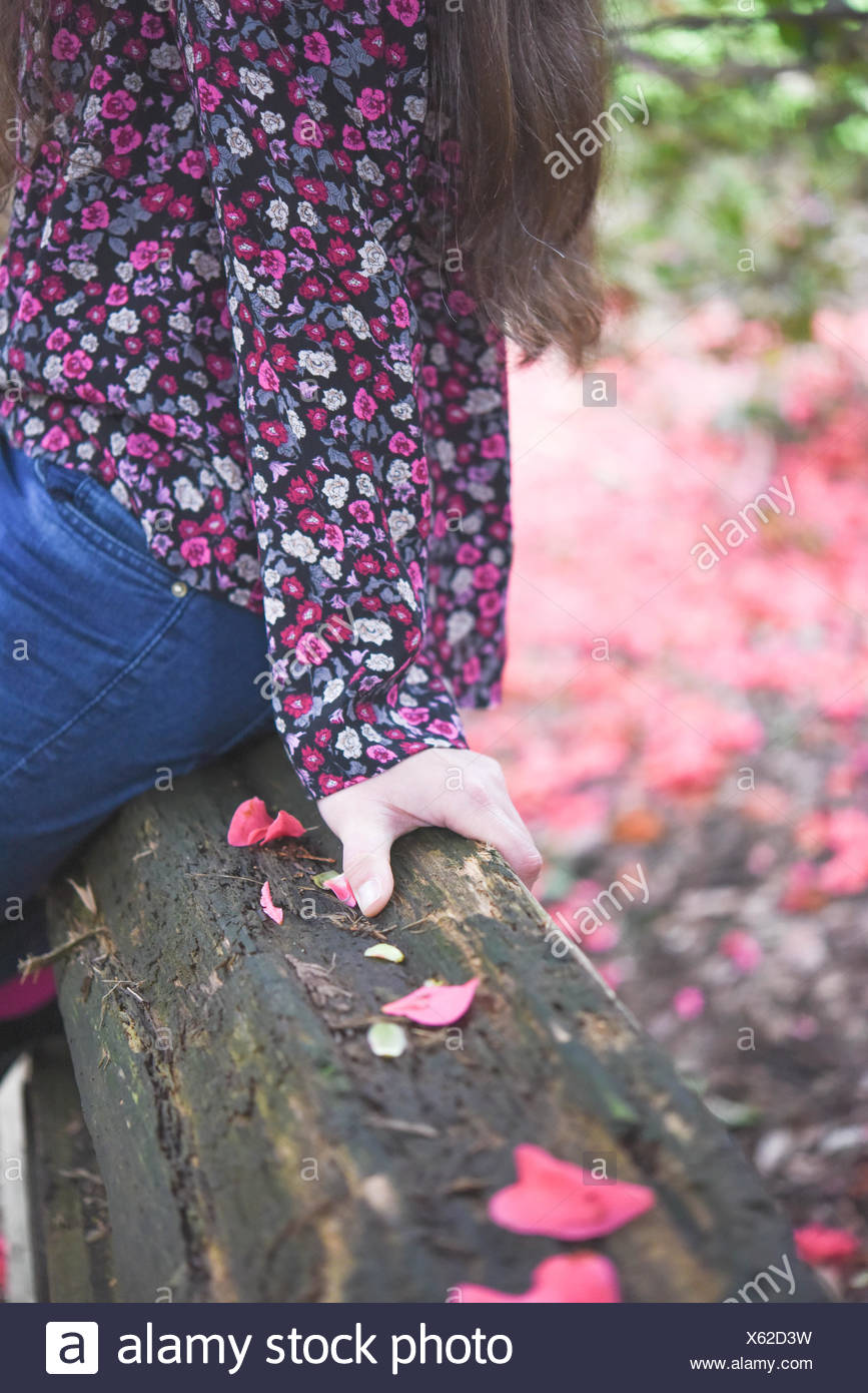 Close-up of part of a woman sitting on a wooden fence, vancouver, Canada - Stock Image