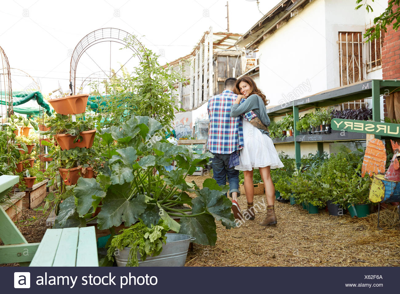 Affectionate couple hugging, walking in plant nursery - Stock Image
