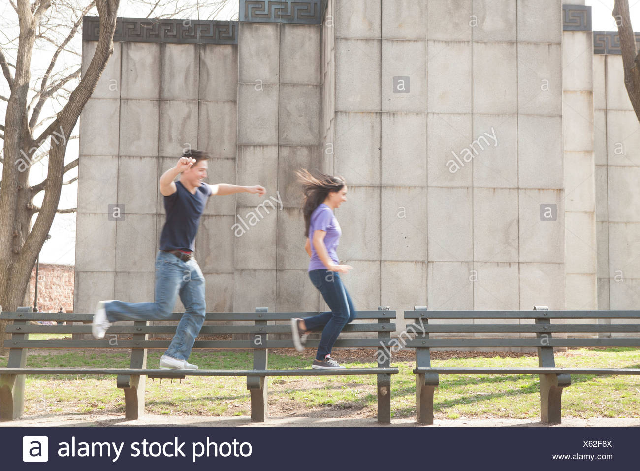 Young couple running along benches - Stock Image