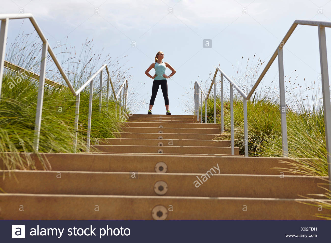 Woman standing at top of stairs - Stock Image