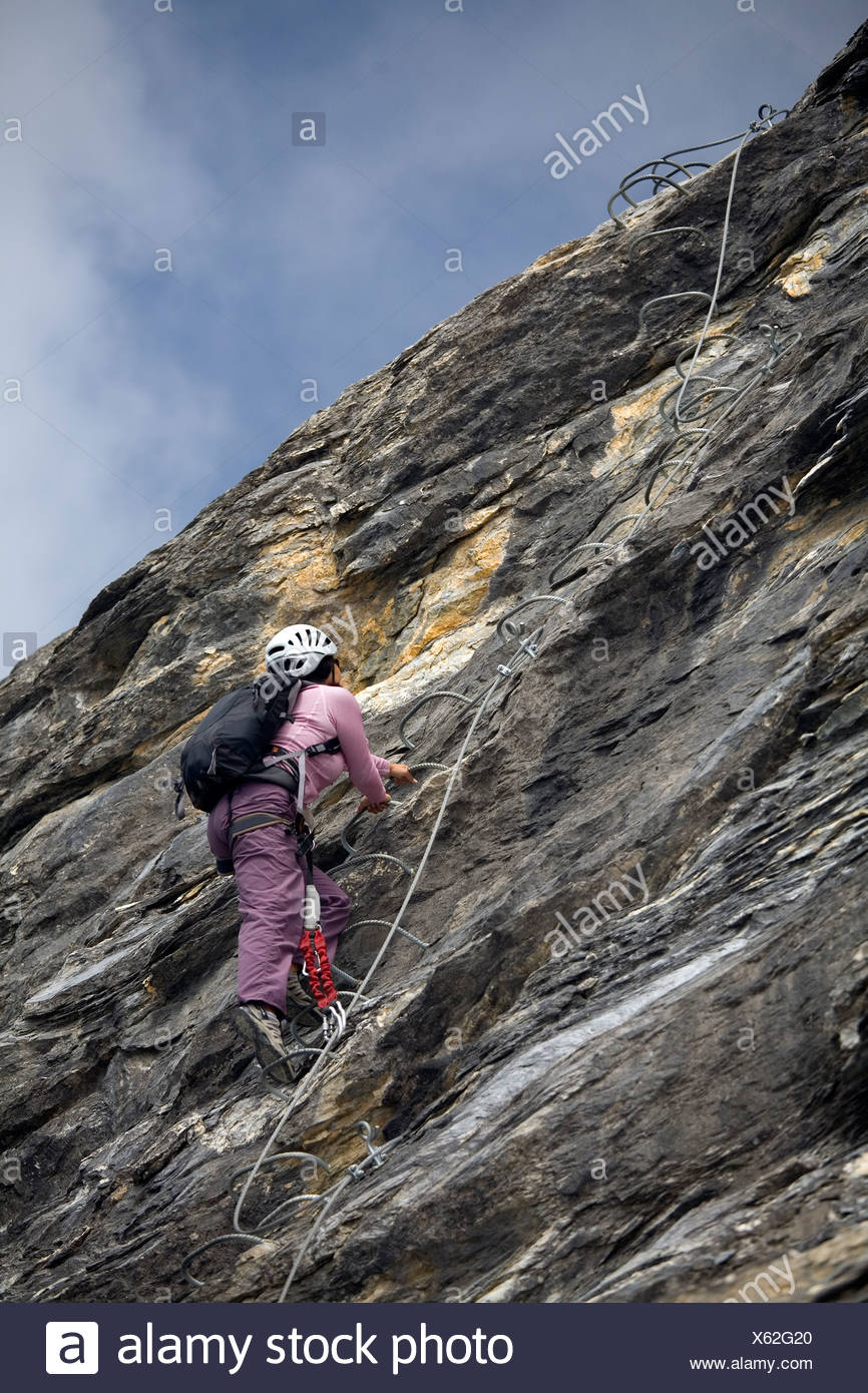 A young woman climbing a ladder embedded in the rock while engaging in the sport of Via Ferrata in the French Alps. - Stock Image