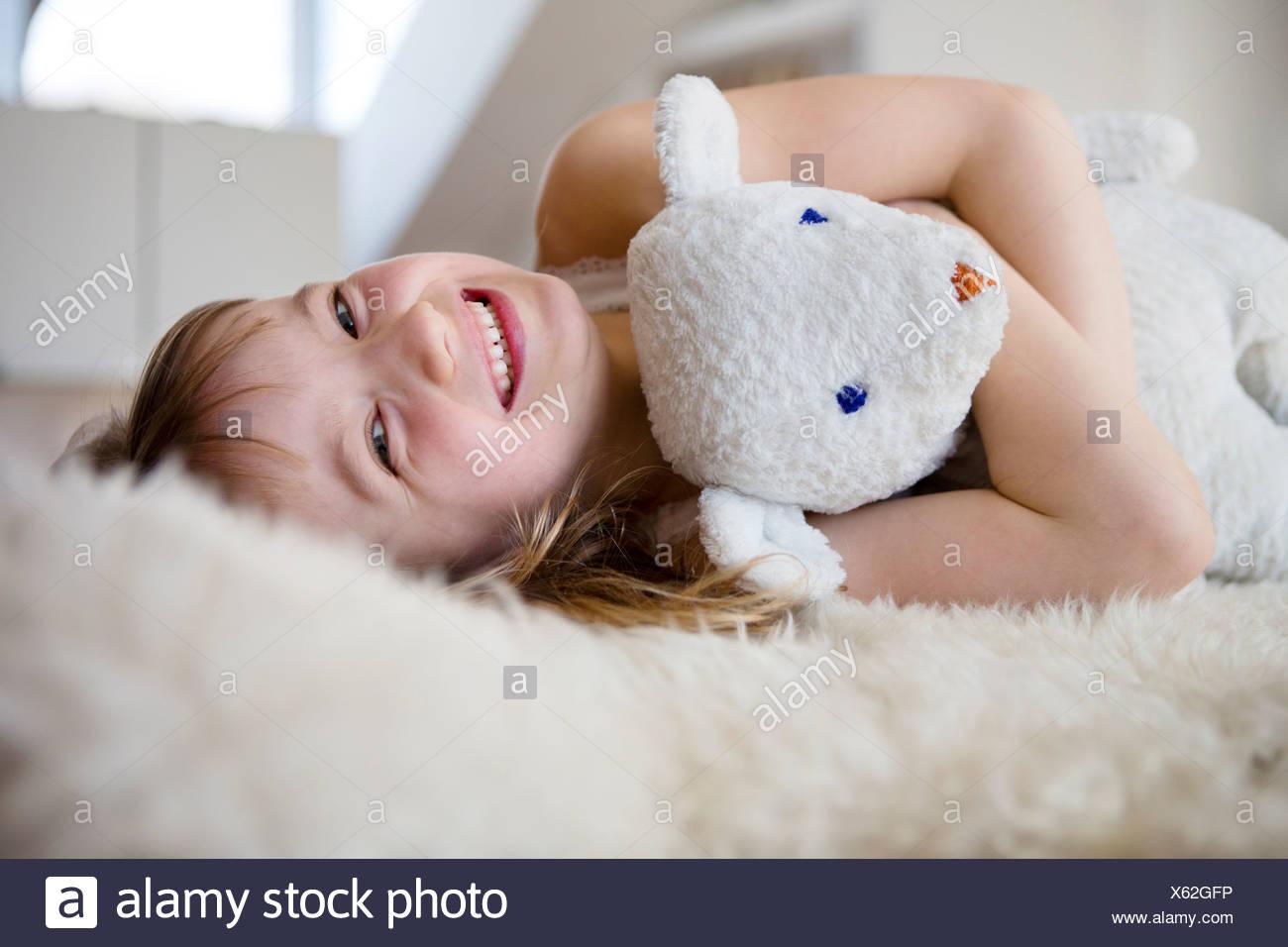 Girl lying on furry bed cuddling teddy bear - Stock Image