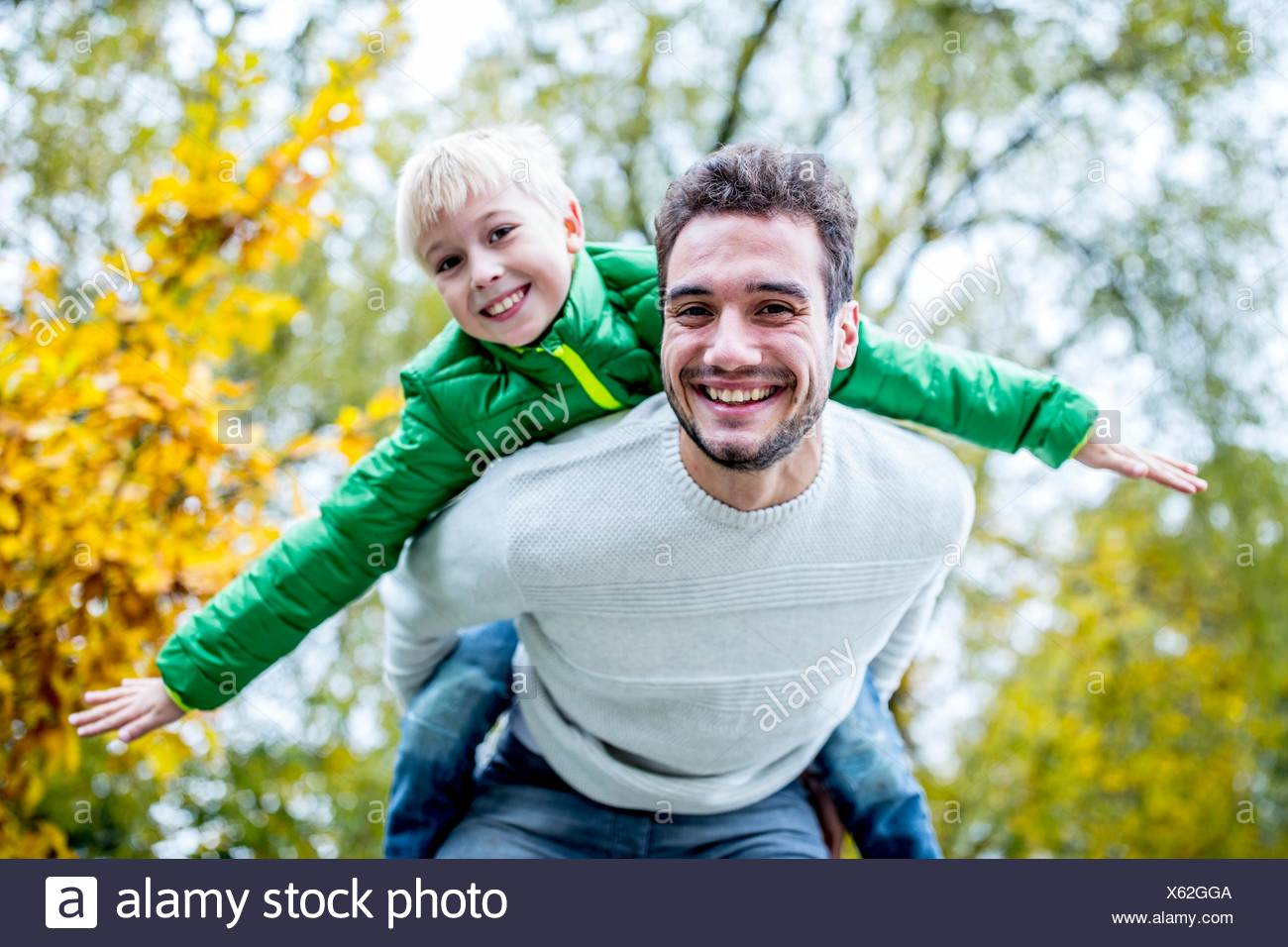 MODEL RELEASED. Father carrying son piggyback in autumn, smiling, portrait. - Stock Image