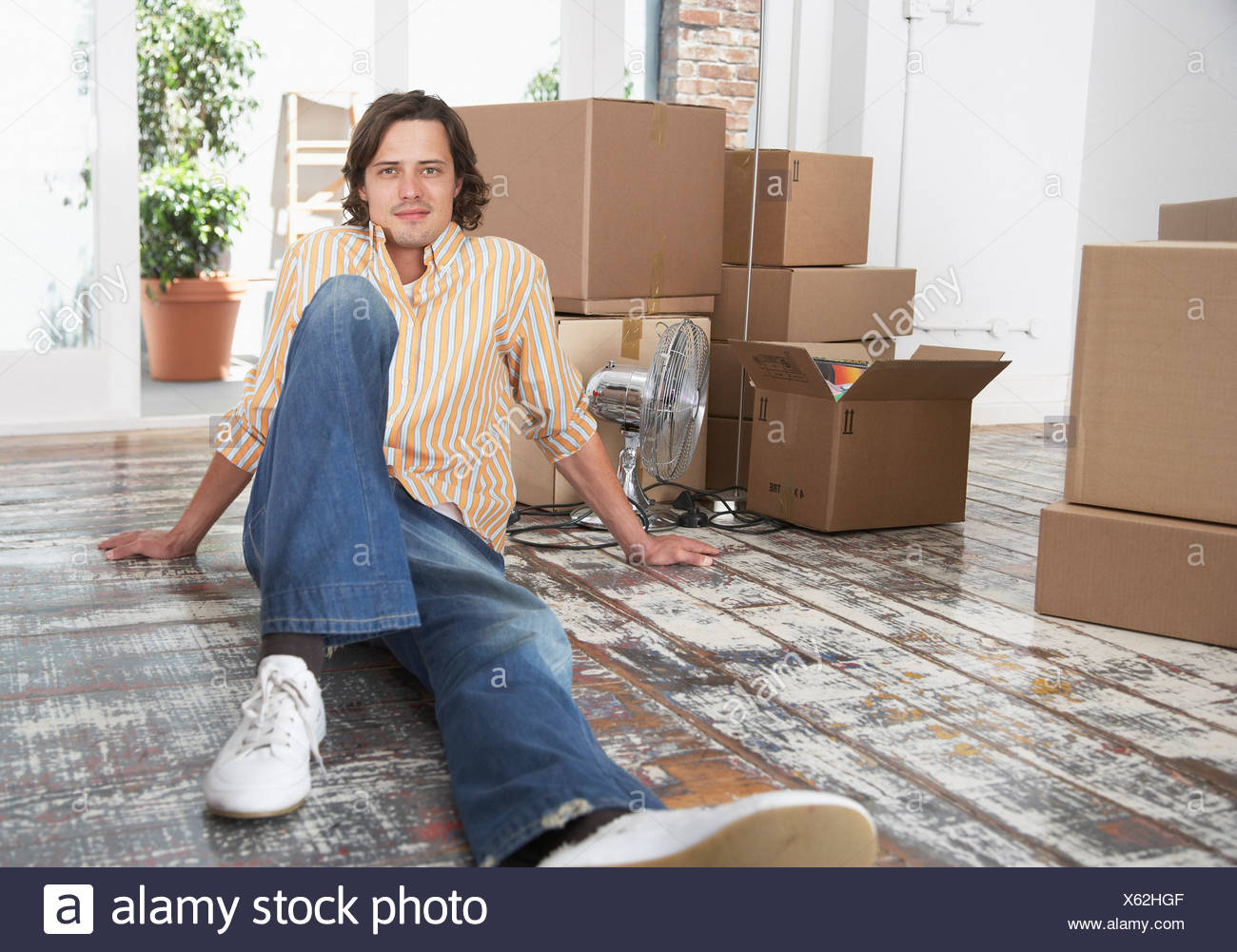 Man sitting on hardwood floor with cardboard boxes and potted plants smiling - Stock Image