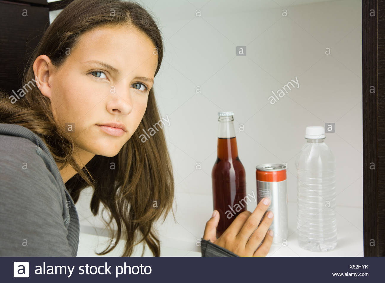 Teen girl next to variety of drinks, reaching for bottled soft drink - Stock Image
