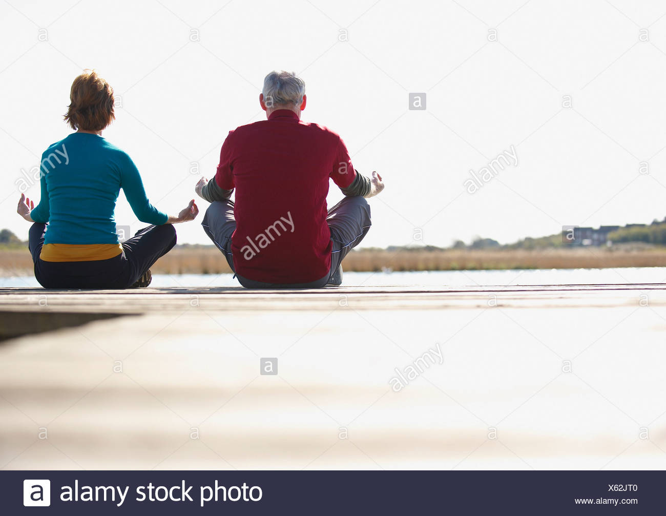 Couple practicing yoga outdoors - Stock Image