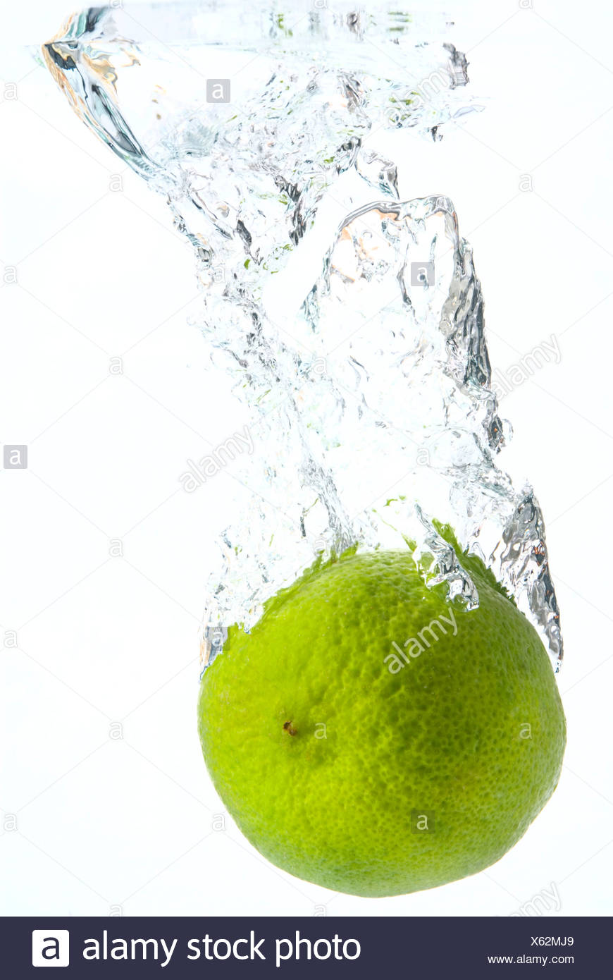 Lime plunging into water - Stock Image