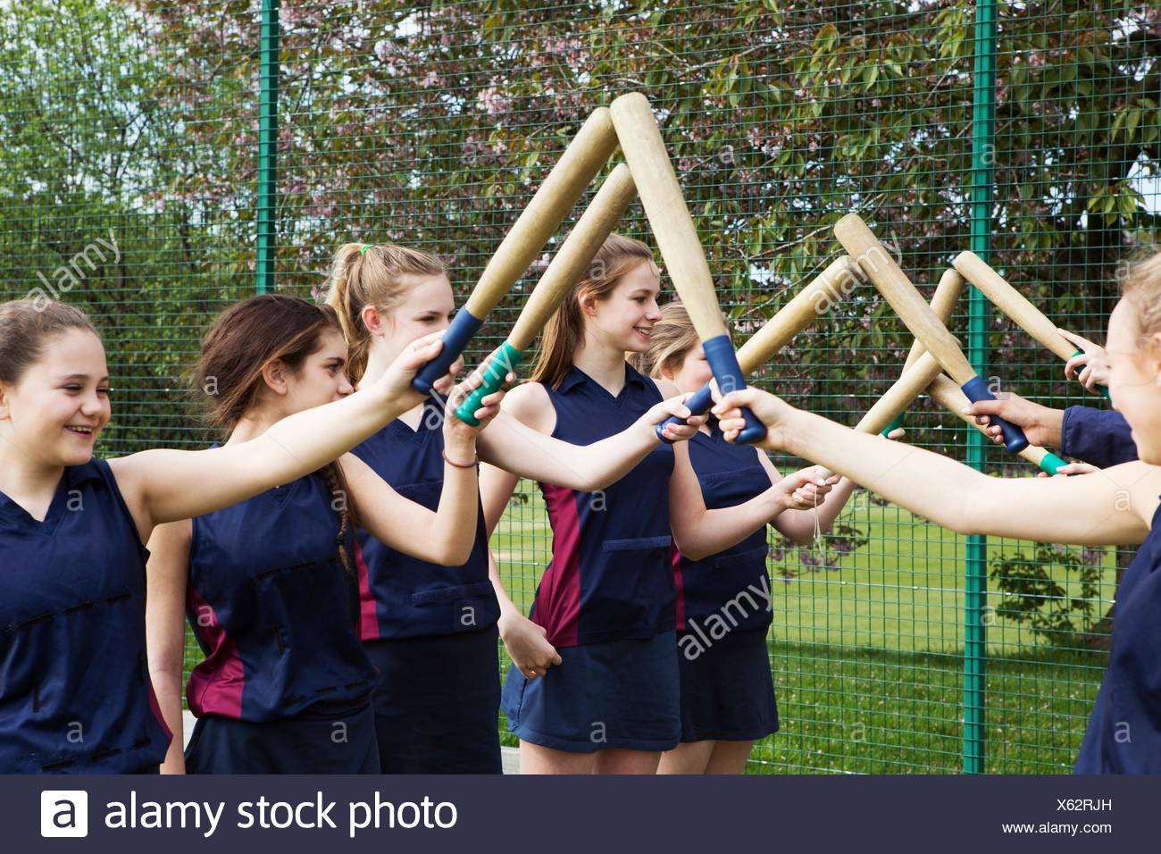 Group of students putting rounders bats together - Stock Image