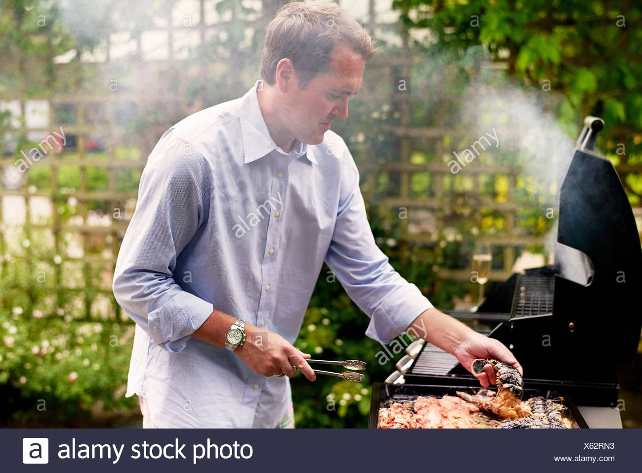 Mature man cooking seafood on barbecue - Stock Image