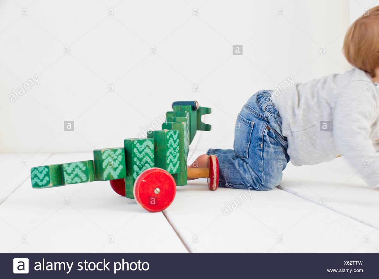 Studio shot of baby girl and wheeled toy - Stock Image