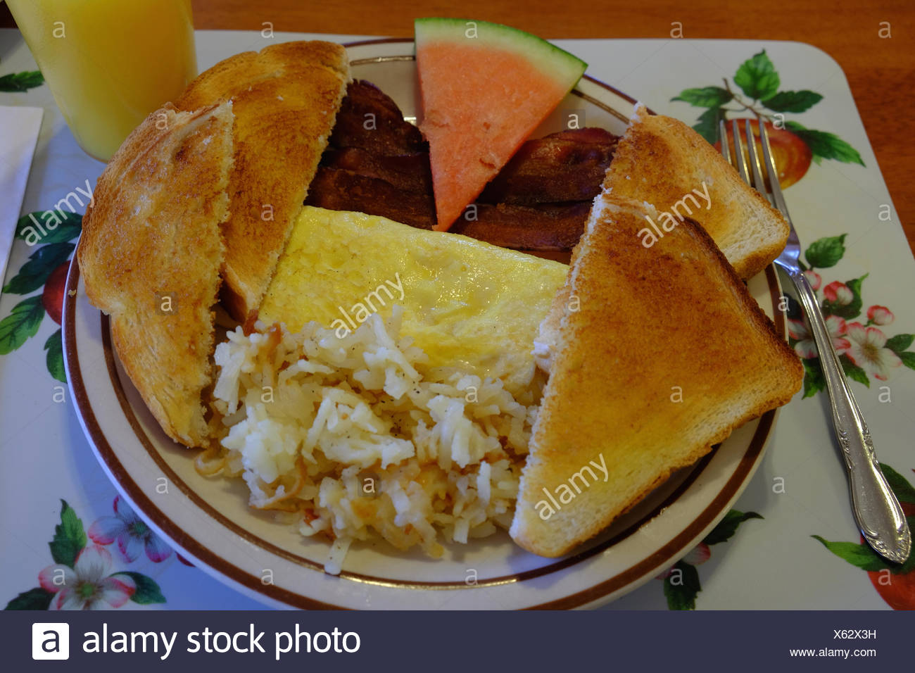 A breakfast of toast, bacon, egg omelet, hash browns, watermelon and orange juice. - Stock Image