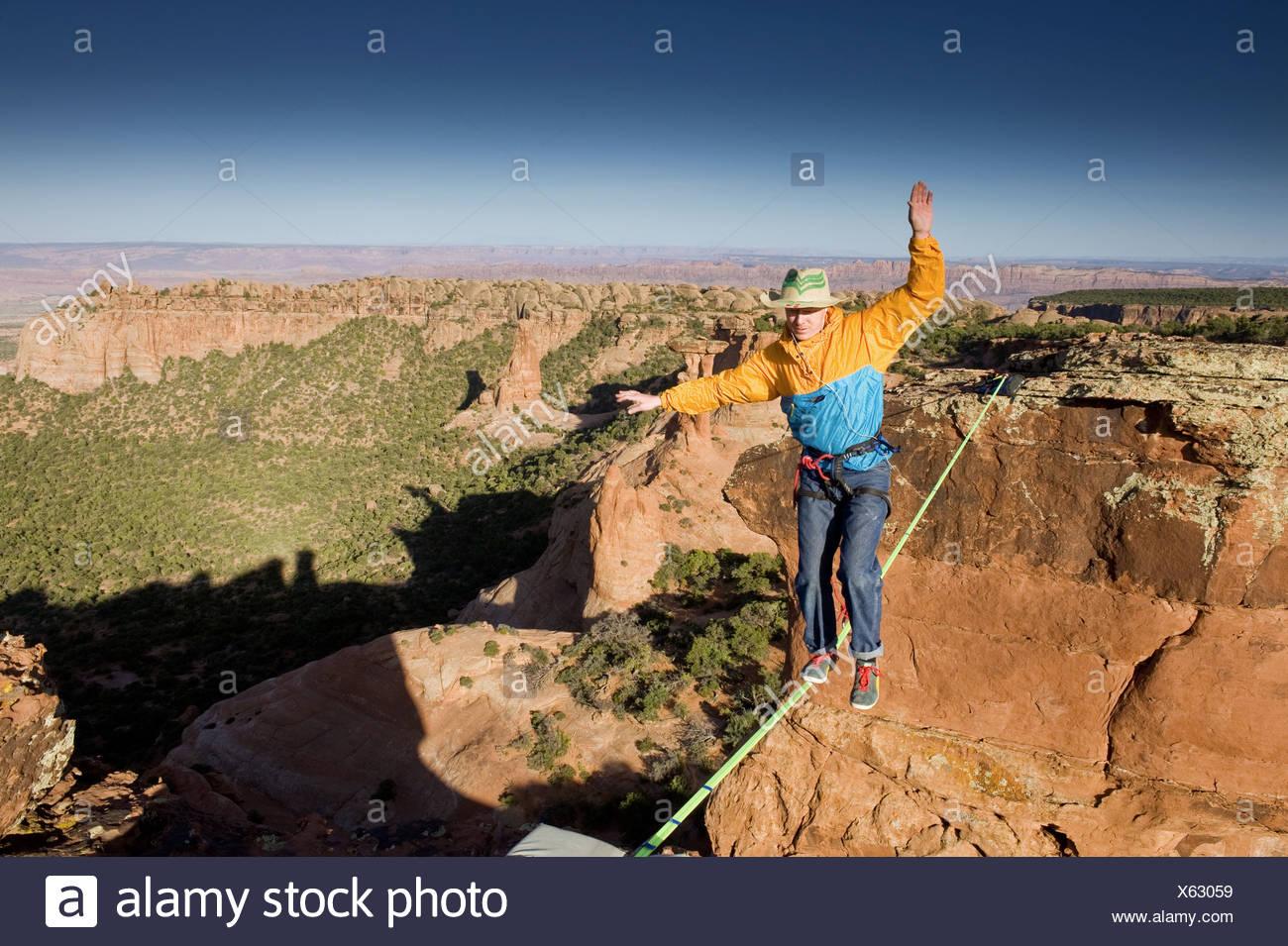 Man highlining, slacklining, between Navaho Sandstone Towers on BLM land near Moab, Utah, USA - Stock Image