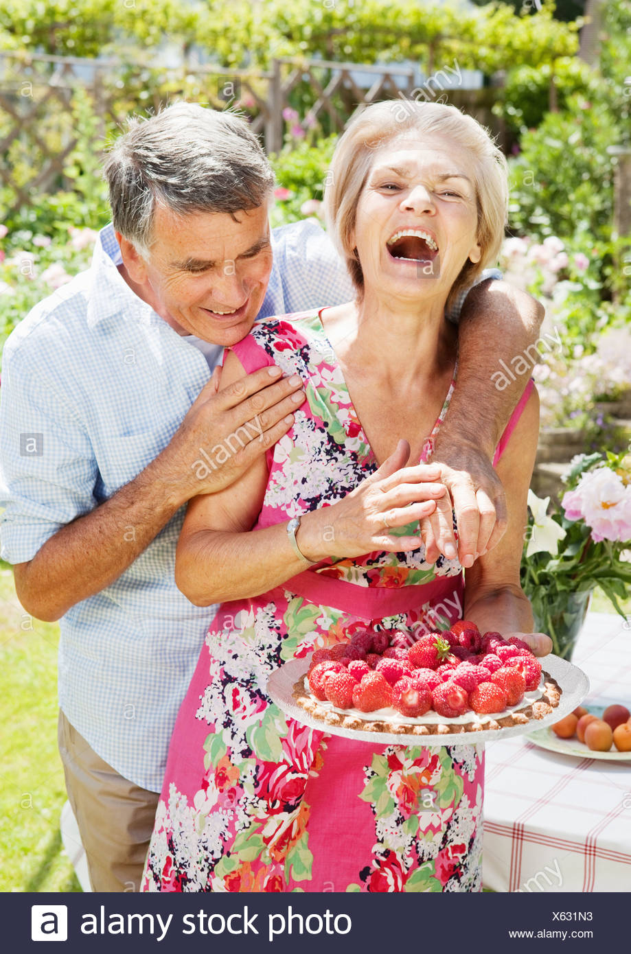 man tries to steal strawberry of tart. - Stock Image