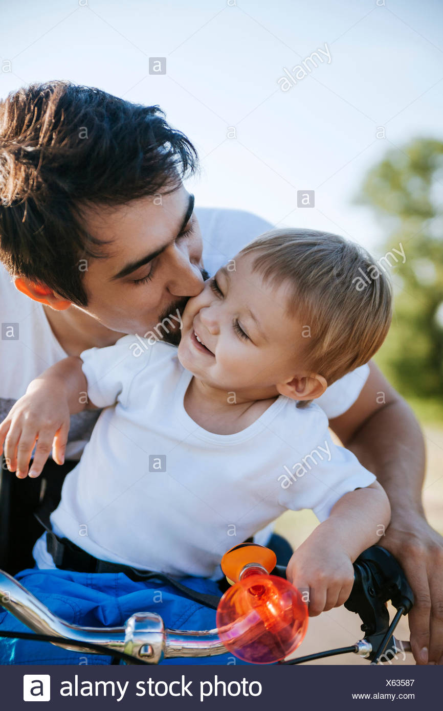 Father kissing his little son on bicycle tour - Stock Image