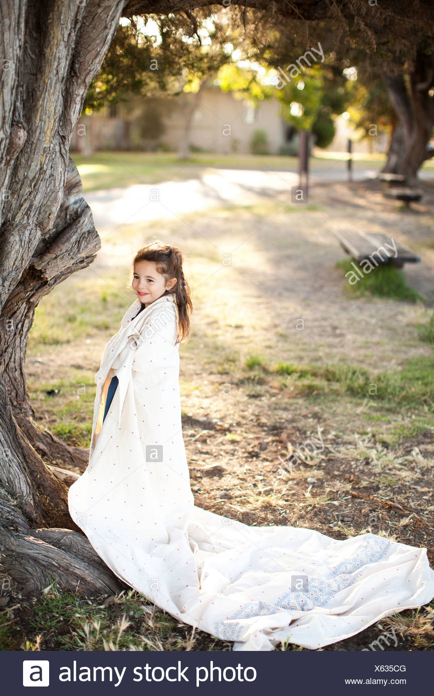 Portrait of girl wrapped in sheet under tree - Stock Image