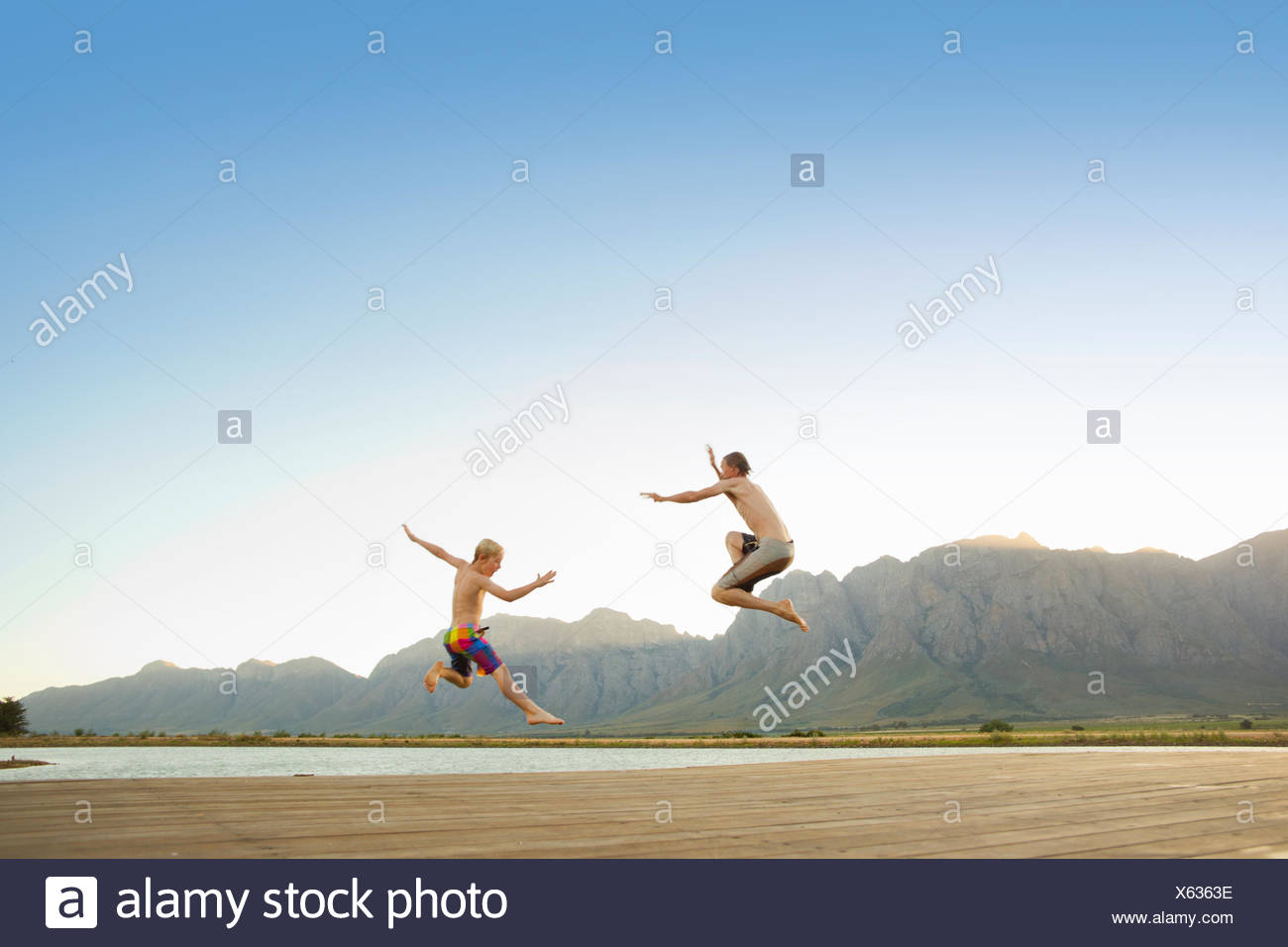 Father and son jumping into lake from jetty - Stock Image