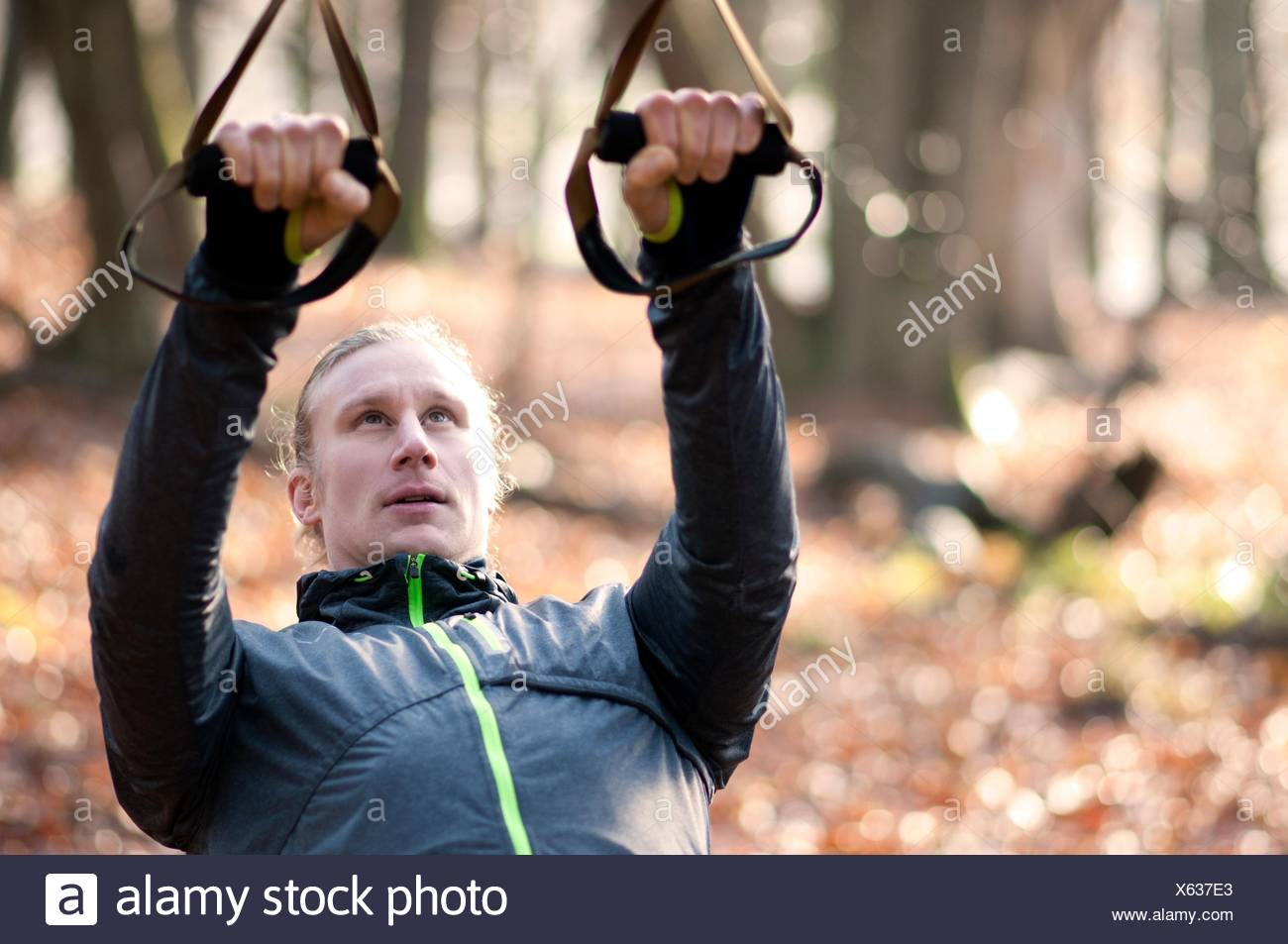 Mid adult man using resistance bands, looking up - Stock Image