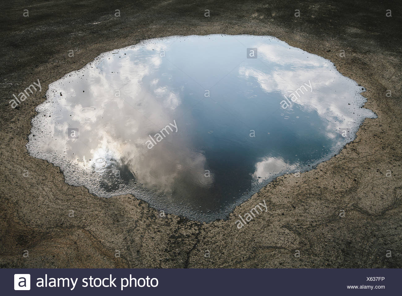 Rain drops falling onto a large puddle A reflection of sky and clouds Elko County Nevada USA - Stock Image
