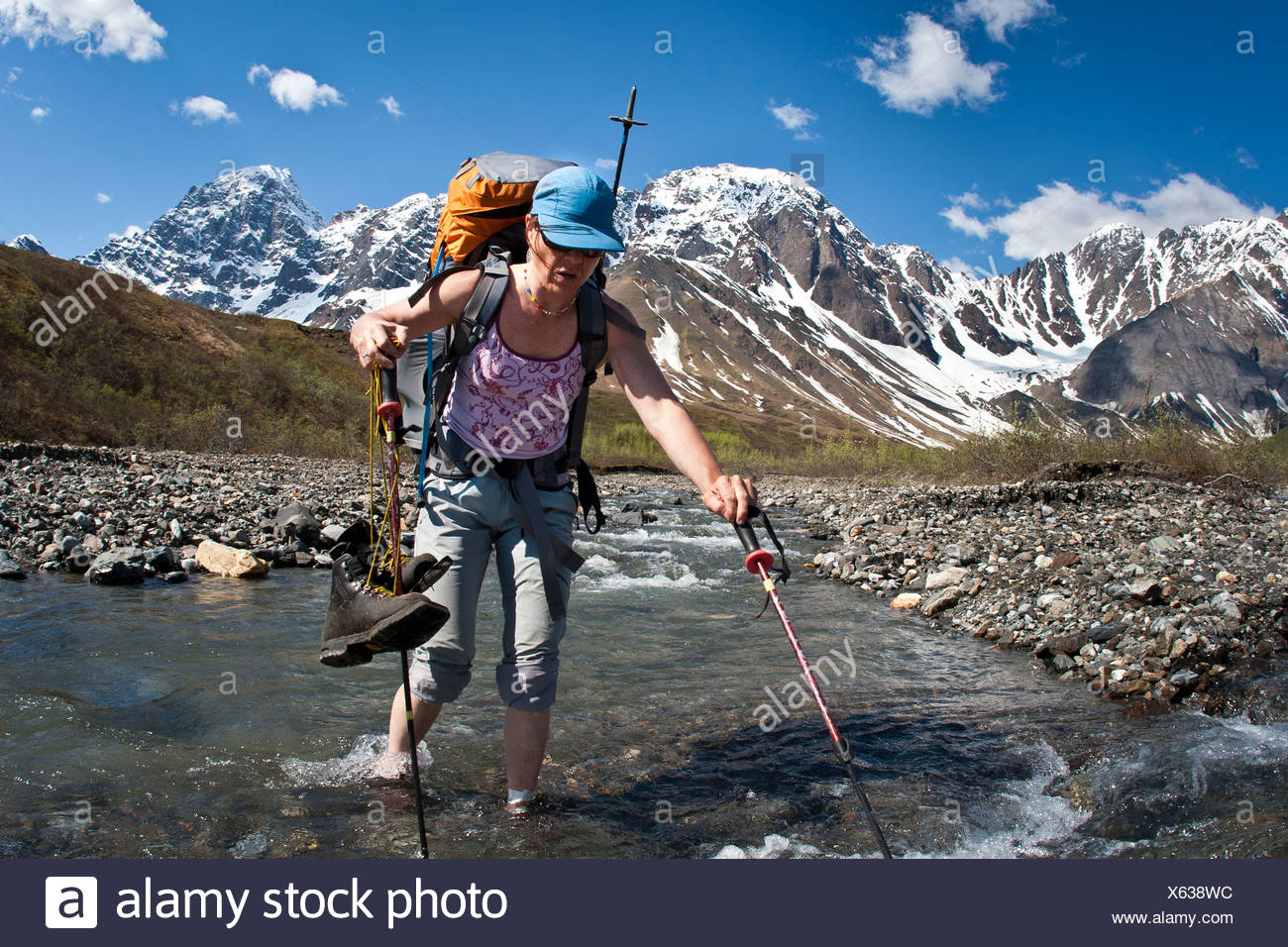 Female backpacker crossing the Babel River below South Buttress on the western flanks of the Revelation Mountains, Alaska Stock Photo